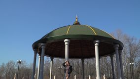 Young girl standing uner the dome in park. Young girl are walking in the park. The girl is going under the dome in square. Pretty female enjoys spring and nature stock video