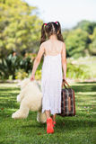 Young girl walking in park with a suitcase and teddy bear Stock Photos