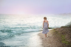 Young girl walking on the sea coast Royalty Free Stock Image