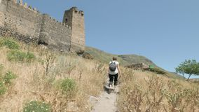 Young girl walking and see Khertvisi fortress - Georgia.  stock video footage