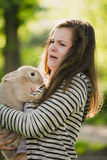 Young girl walking in spring, summer park with her bunny and scared. Royalty Free Stock Photo