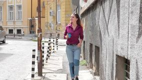 Young girl walking on the street in the old town stock video footage