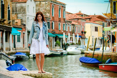 Young girl walking streets of Murano. Caucasian woman in the beautiful setting of the murano island in the venetian lagoon Stock Images