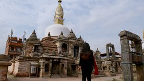Young girl walking towards old ancient ruins of Buddhist Gompa in ancient city of Kathmandu,