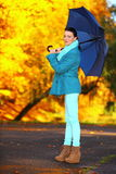 Young girl walking with umbrella in autumnal park Royalty Free Stock Photo