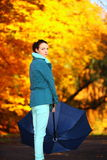 Young girl walking with umbrella in autumnal park Stock Photography