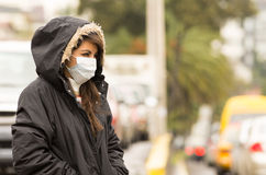 Young girl walking wearing jacket and a mask in Stock Image