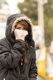 Young girl walking wearing jacket and a mask in Royalty Free Stock Photo
