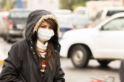 Young girl walking wearing jacket and a mask in Royalty Free Stock Photography