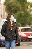 Young girl walking wearing a mask in the city Royalty Free Stock Images
