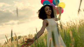 Young girl walking through a wheat field with colour balloons during sunset stock footage