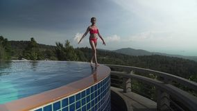 Young girl walks along side of the pool atop a mountain stock footage video. Young girl walks along the side of the atop a mountain stock footage video stock video