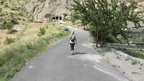 Young girl walks in cave monastery Vardzia - Georgia.  stock footage