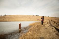 A young girl walks with a dog on the shore of a lake royalty free stock image