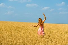 Young girl walks on a field royalty free stock image