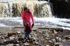 A young girl walks with her child at the waterfall royalty free stock photography