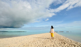 Young girl walks on long narrow beach Stock Photos