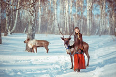 Young girl walks with a reindeer in the winter day Stock Photos
