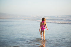 A young girl walks through shallow water Royalty Free Stock Photo