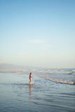A young girl walks through shallow water Stock Image