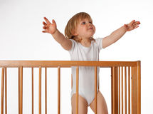 Young girl wants to be taken out from cot Royalty Free Stock Photos