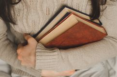 Young girl holds two books in hands. Young girl in a warm beige sweater holds books in hands Stock Images
