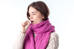 Young girl in  warm scarf stands sideways and coughs isolated on white background Royalty Free Stock Photo
