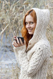 Young girl in warm sweater drinking a cup of hot drink. Young girl in warm white sweater drinking a cup of hot drink Stock Photos
