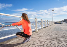 Young girl warming before running in a promenade Stock Images