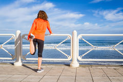 Young girl warming before running in a promenade Royalty Free Stock Photos