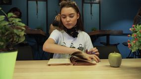 Beautiful young girl was flipping through a book, then suddenly get nervous and threw the book to the floor with her. Young girl was flipping through a book stock video