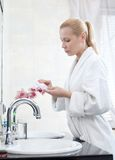 Young girl washes face with lotion. Wearing with bath gown girl washes face with lotion Stock Image