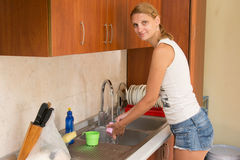 A young girl washes the glasses in the kitchen and looked in the frame Stock Photo