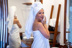 A young girl washes her face. The girl s head and body are wrapped in white towels royalty free stock images