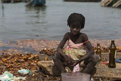 Young girl washing bottles next to the water in the port of the city of Cacheu, in Guinea Bissau. royalty free stock photo