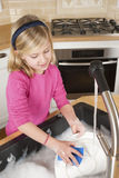 Young girl washing dishes. In sink with blue sponge. Looking down while scrubbing plate stock image