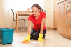 Young girl washing floor in kitchen. Stock Image