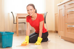 Young girl washing floor in kitchen. Royalty Free Stock Images