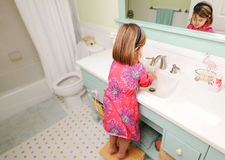 Young girl washing hands in bathroom stock images