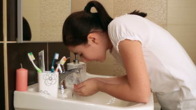 Young girl washing her face
