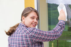 Young girl washing windows outside Royalty Free Stock Image