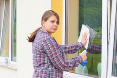 Young girl washing windows outside Royalty Free Stock Photos