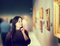 Young girl watching at art collection exhibition. In museum stock images