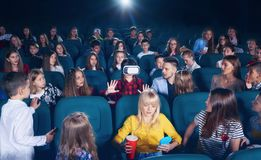 Young girl watching 3D-eyeglasses in cinema hall. Cinema hall full of young people and children,looking surprised and exited, watching on girl wearing 3D stock photos