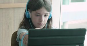 Young girl watching her tablet computer smiles at the camera stock footage