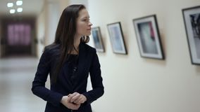 Young girl watching photos in the photo gallery. Elegant beautiful woman looks at the pictures in the museum of modern. Art. Work of art paintings on the stock footage