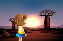 A young girl watching the sunset at the desert Royalty Free Stock Photography