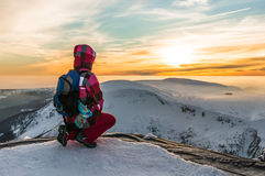 Young girl watching at the sunset on the top of mountains Royalty Free Stock Image