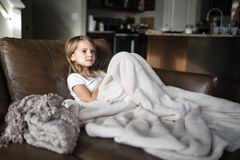 Young girl watching television. Young girl sitting on the couch under the blanket watching television Royalty Free Stock Images