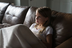 Young girl watching television. Young girl sitting on the couch under the blanket watching television Stock Photos